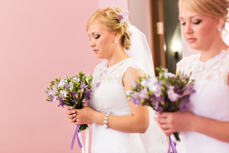 La muchacha hermosa de la novia con el peinado y el maquillaje brillante mira en el espejo fotos de archivo libres de regalías