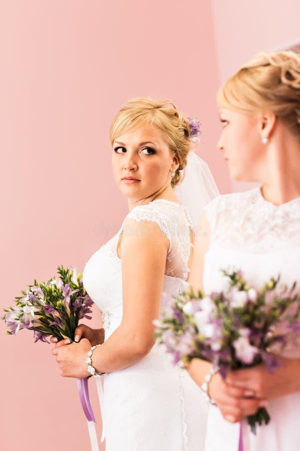 La muchacha hermosa de la novia con el peinado y el maquillaje brillante mira en el espejo imagen de archivo