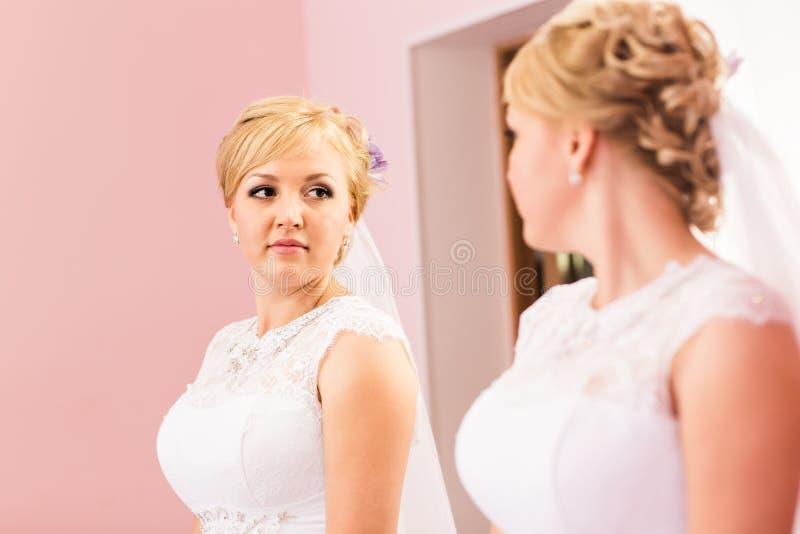 La muchacha hermosa de la novia con el peinado y el maquillaje brillante mira en el espejo imagen de archivo libre de regalías