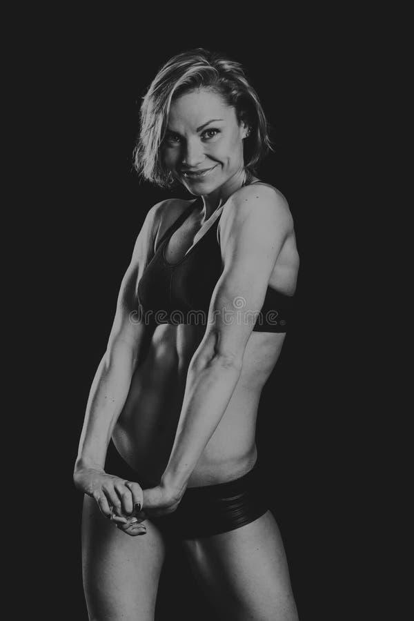 La muchacha hermosa de los deportes en un fondo oscuro fotos de archivo libres de regalías