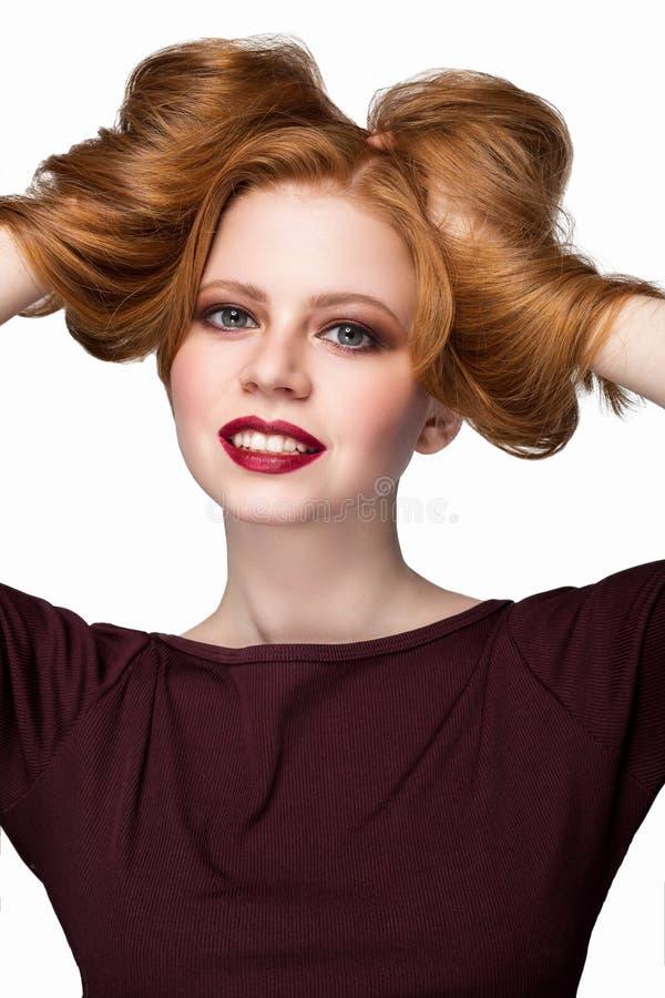 La muchacha hermosa del pelirrojo con una sonrisa que mira las manos felices de la cámara y las elevaciones el pelo aíslan el pri fotos de archivo libres de regalías