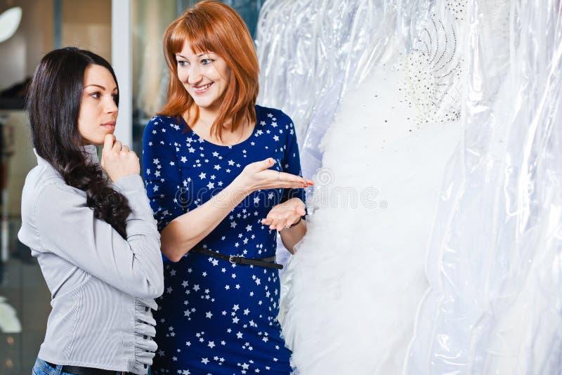 La muchacha hermosa elige su vestido de boda Retrato en el sa nupcial imagenes de archivo