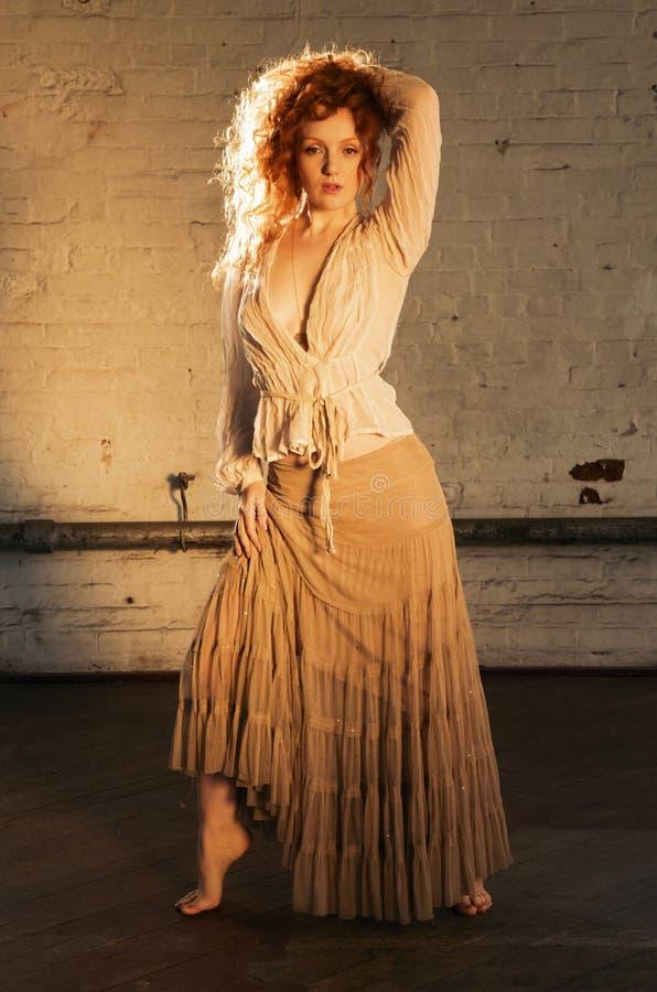 La muchacha hermosa en actitud sensual con el pelo rojo ondulado largo destacó en luz del sol fotografía de archivo libre de regalías