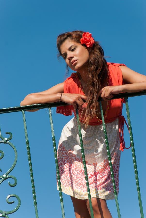 La muchacha hermosa en el balcón con el vestido de la moda y el pelo florecen imagen de archivo