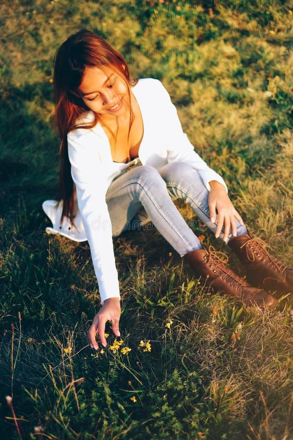 La muchacha hermosa en el prado que se sienta en la cosecha de la hierba florece imágenes de archivo libres de regalías