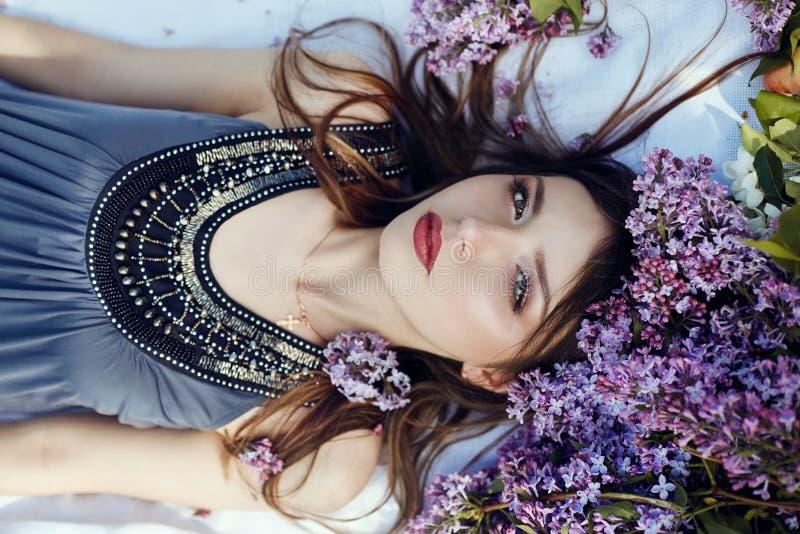 La muchacha hermosa en el vestido que plantea la mentira en lila ramifica en un día de verano, flores púrpuras en el parque Retra foto de archivo