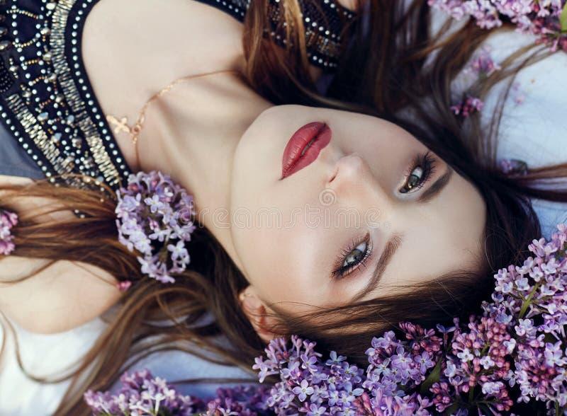 La muchacha hermosa en el vestido que plantea la mentira en lila ramifica en un día de verano, flores púrpuras en el parque Retra imagenes de archivo