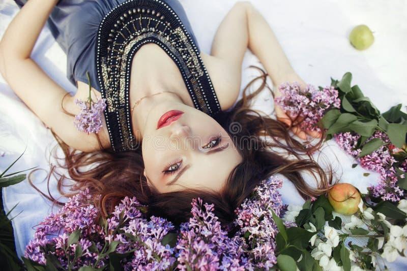 La muchacha hermosa en el vestido que plantea la mentira en lila ramifica en un día de verano, flores púrpuras en el parque Retra fotografía de archivo