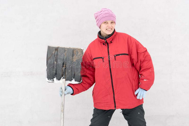 La muchacha hermosa en ropa de la moda del invierno con una pala despeja el camino de la nieve Familia, tradición, día de fiesta foto de archivo libre de regalías