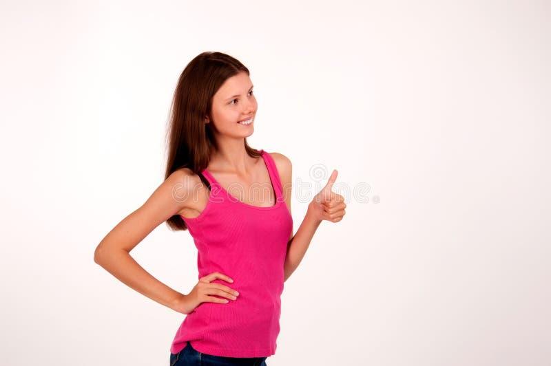 La muchacha hermosa en un fondo blanco muestra un gesto con un pulgar para arriba foto de archivo