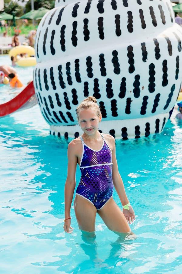 La muchacha hermosa en un traje de baño nada en la piscina foto de archivo