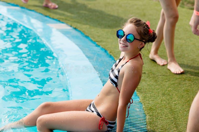 La muchacha hermosa en un traje de baño nada en la piscina imagen de archivo