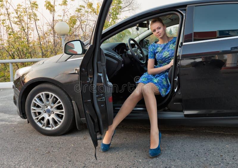 La muchacha hermosa en un vestido azul en una cabina del coche foto de archivo