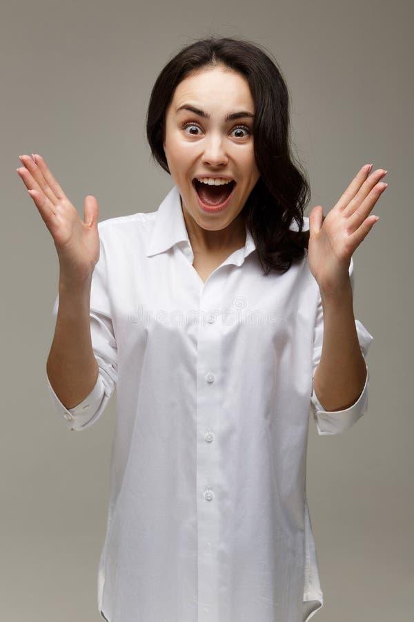 La muchacha hermosa en una camisa blanca muestra las emociones - sorpresa, choque, en un fondo ligero foto de archivo libre de regalías