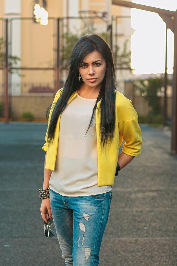 La muchacha hermosa en una chaqueta amarilla y vaqueros sostiene los vidrios imagen de archivo libre de regalías