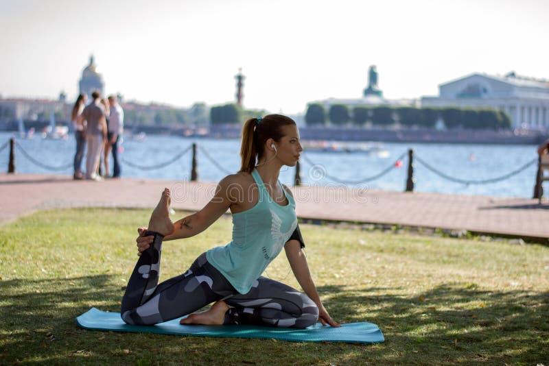 La muchacha hermosa en una deporte-colocación viste y los auriculares que hacen aptitud o yoga en la costa en St Petersburg imagenes de archivo
