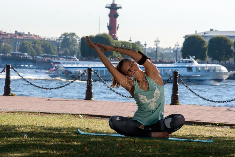 La muchacha hermosa en una deporte-colocación viste y los auriculares que hacen aptitud o yoga en la costa en St Petersburg foto de archivo libre de regalías