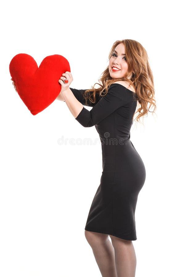 La muchacha hermosa en vestido negro con rojo oye en un fondo blanco imagen de archivo