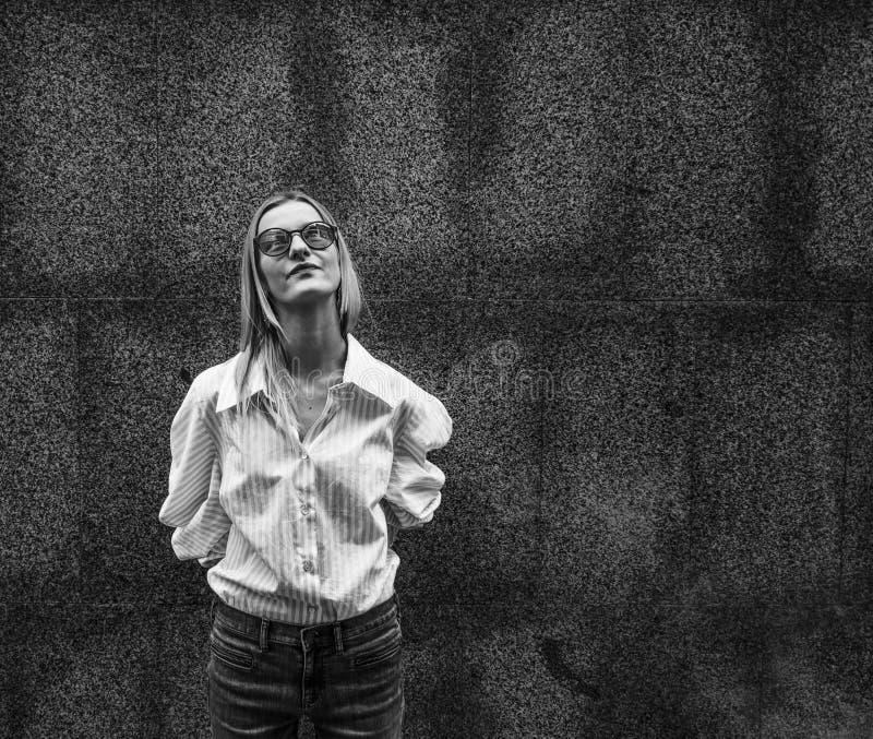 La muchacha hermosa en vidrios con placer fuma un vape Día, al aire libre imágenes de archivo libres de regalías