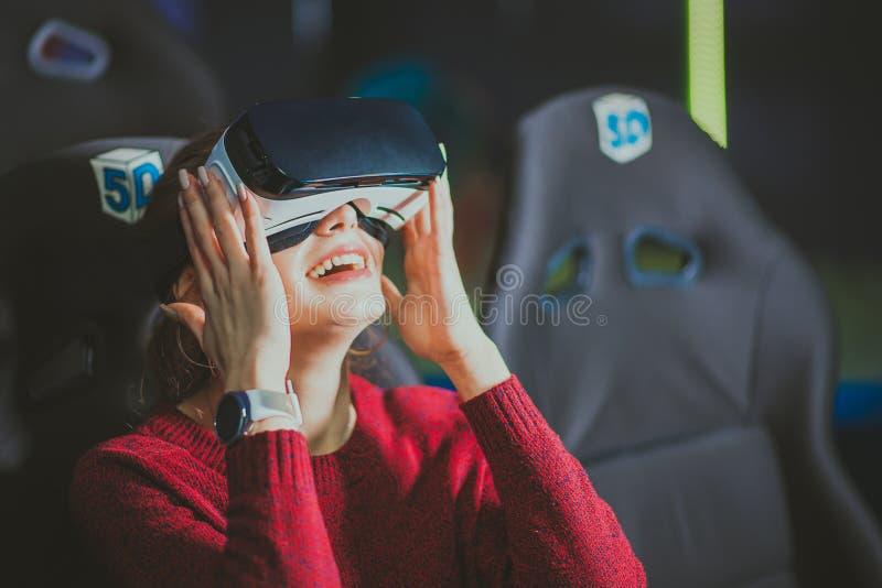 La muchacha hermosa en vidrios virtuales está mirando una película con speci imagen de archivo