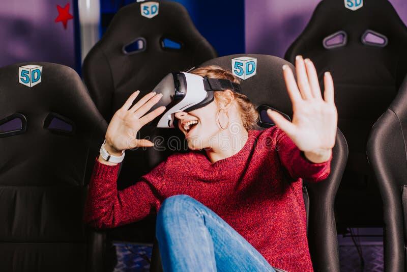 La muchacha hermosa en vidrios virtuales está mirando una película con speci imágenes de archivo libres de regalías