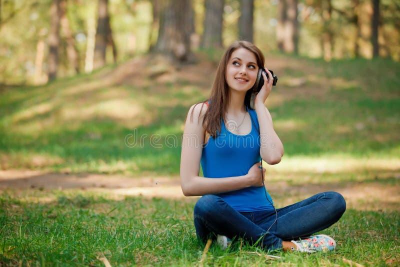 La muchacha hermosa escucha música imagen de archivo