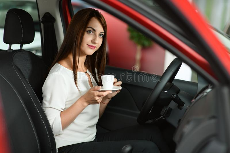 La muchacha hermosa está bebiendo el café en el nuevo coche foto de archivo libre de regalías