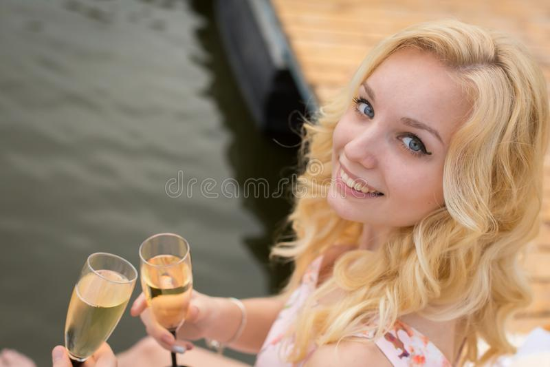 La muchacha hermosa está bebiendo un vidrio de champán imagenes de archivo