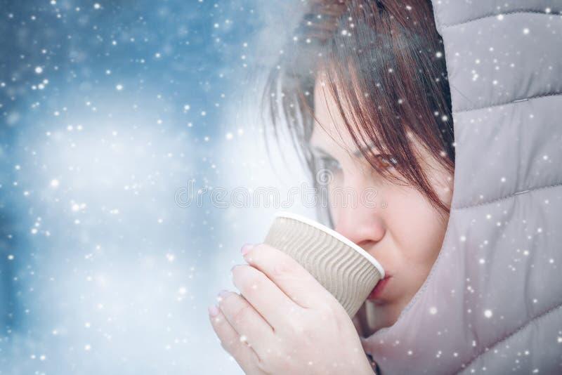 La muchacha hermosa está bebiendo una bebida caliente de una taza en el invierno en la naturaleza, té, café El nevar al aire libr fotos de archivo libres de regalías