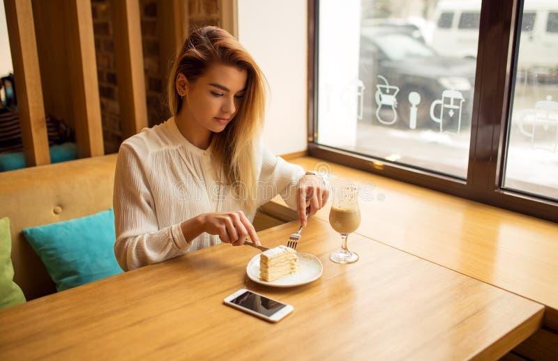 La muchacha hermosa está comiendo la torta fotos de archivo