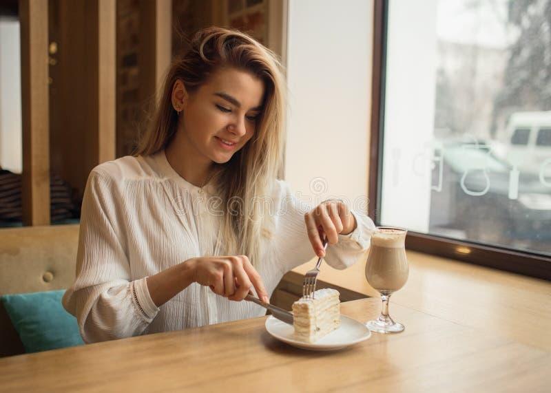 La muchacha hermosa está comiendo la torta y la sonrisa imagen de archivo libre de regalías