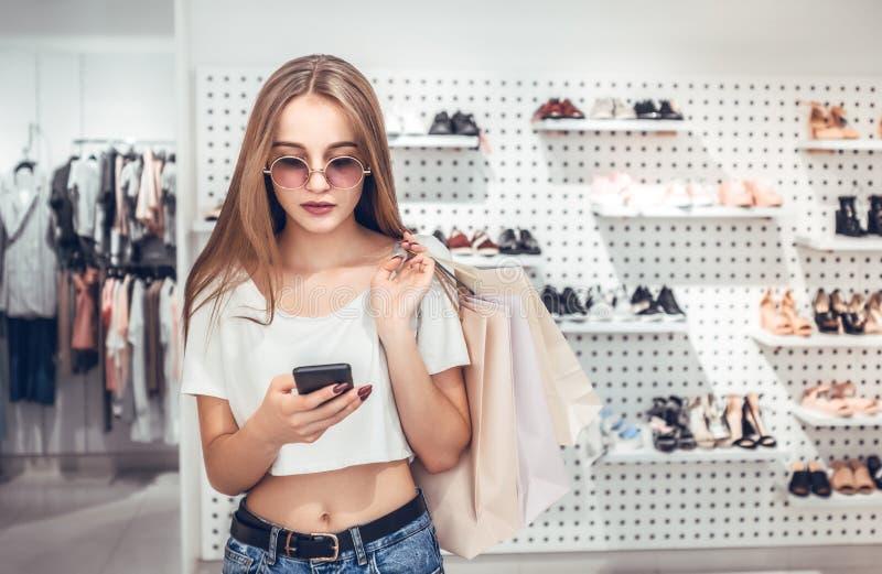 La muchacha hermosa está sosteniendo bolsos de compras en boutique fotografía de archivo