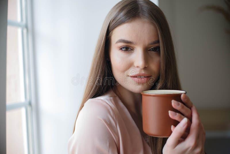 La muchacha hermosa est? bebiendo el caf? y est? sonriendo mientras que se sienta en el caf? fotografía de archivo libre de regalías