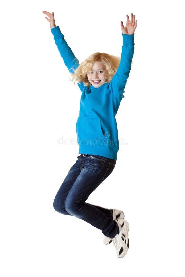 La muchacha hermosa feliz joven salta en el aire. foto de archivo