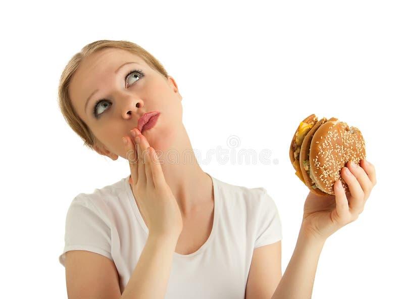 La muchacha hermosa hambrienta come una hamburguesa sabrosa imagen de archivo