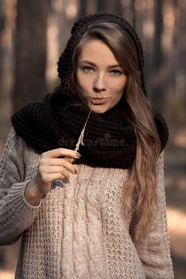La muchacha hermosa, impresionante, bonita, agradable, atractiva, feliz, sonriente en el suéter caliente, sombrero, bufanda en el imágenes de archivo libres de regalías