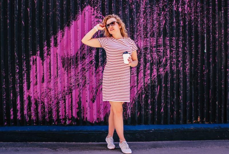 La muchacha hermosa joven bebe el café en el verano al aire libre foto de archivo libre de regalías