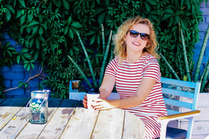 La muchacha hermosa joven bebe el café en el verano al aire libre en una tabla imagen de archivo