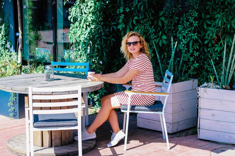 La muchacha hermosa joven bebe el café en el verano al aire libre en una tabla imagen de archivo libre de regalías