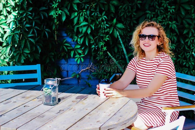 La muchacha hermosa joven bebe el café en el verano al aire libre en una tabla foto de archivo