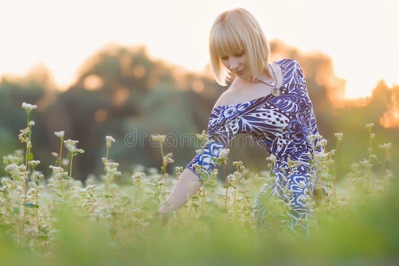 La muchacha hermosa joven camina en el campo floreciente del alforfón imagenes de archivo