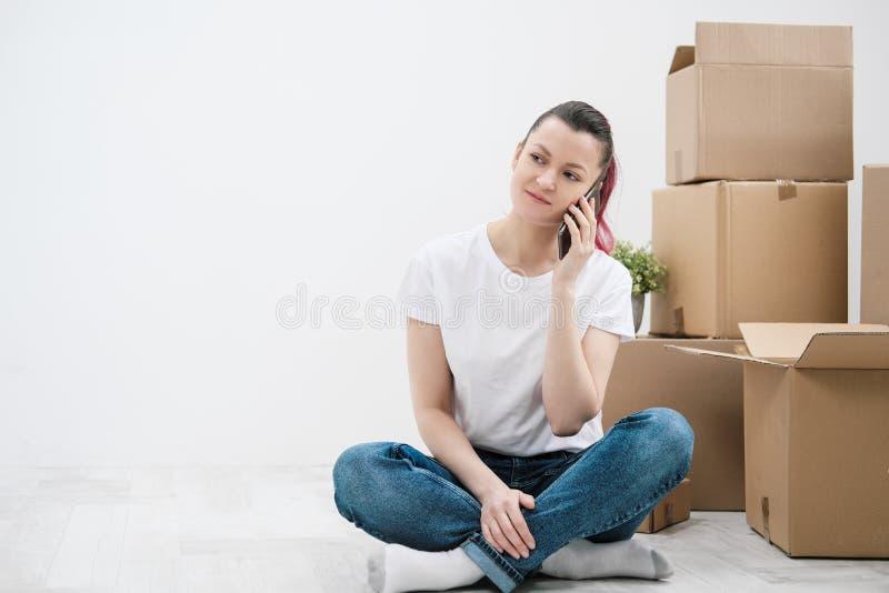 La muchacha hermosa joven con el pelo coloreado en una camiseta blanca y vaqueros, hablando en el teléfono y escribe mensajes con imágenes de archivo libres de regalías