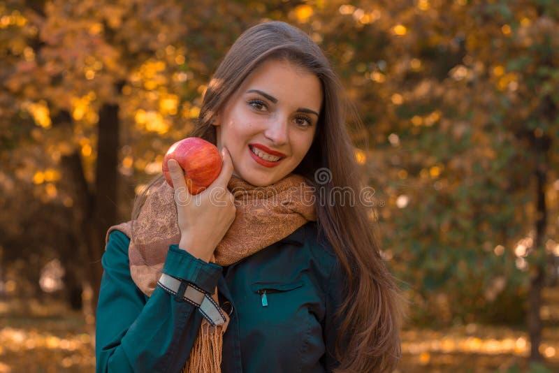La muchacha hermosa joven con el pelo largo en una camisa oscura y una bufanda caliente guarda sonrisas delanteras de las miradas fotografía de archivo