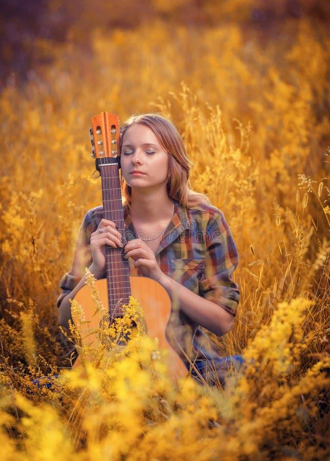La muchacha hermosa joven con los ojos cerrados se sienta en un campo en un acou imágenes de archivo libres de regalías
