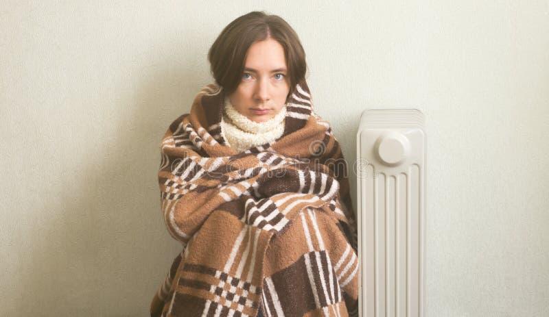 La muchacha hermosa joven congeló y calienta las manos cerca de un radiador, vestido en tela escocesa de lana caliente imagenes de archivo