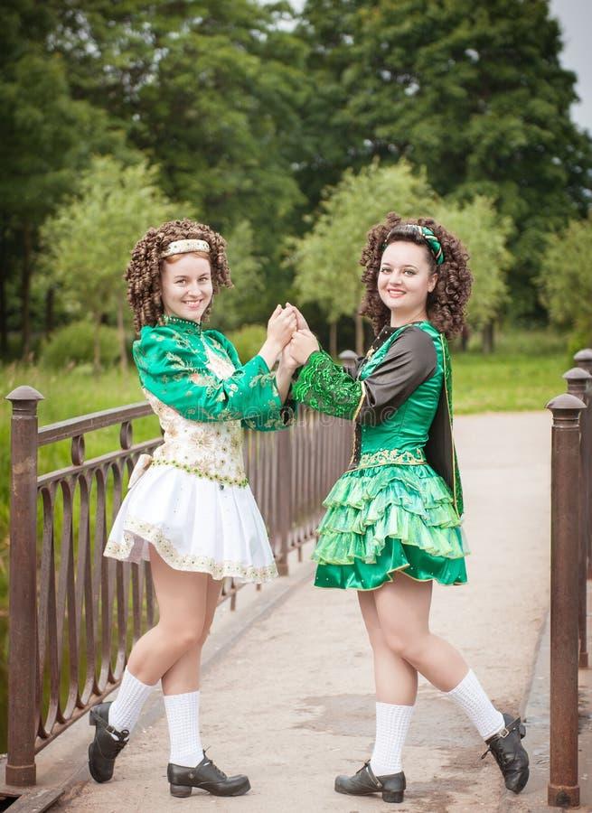 La muchacha hermosa joven dos en irlandés baila la presentación del vestido al aire libre imagen de archivo libre de regalías