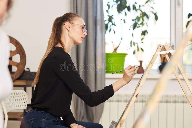La muchacha hermosa joven en los vidrios vestidos en blusa negra y vaqueros se sienta en el caballete y pinta una imagen en el di foto de archivo