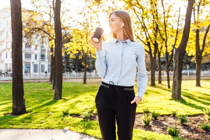 La muchacha hermosa joven, en ropa oficial, café de las bebidas, escucha imagen de archivo