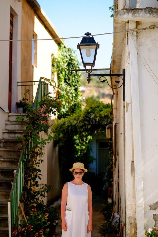 La muchacha hermosa joven en sombrero de paja camina a través de las calles estrechas imágenes de archivo libres de regalías