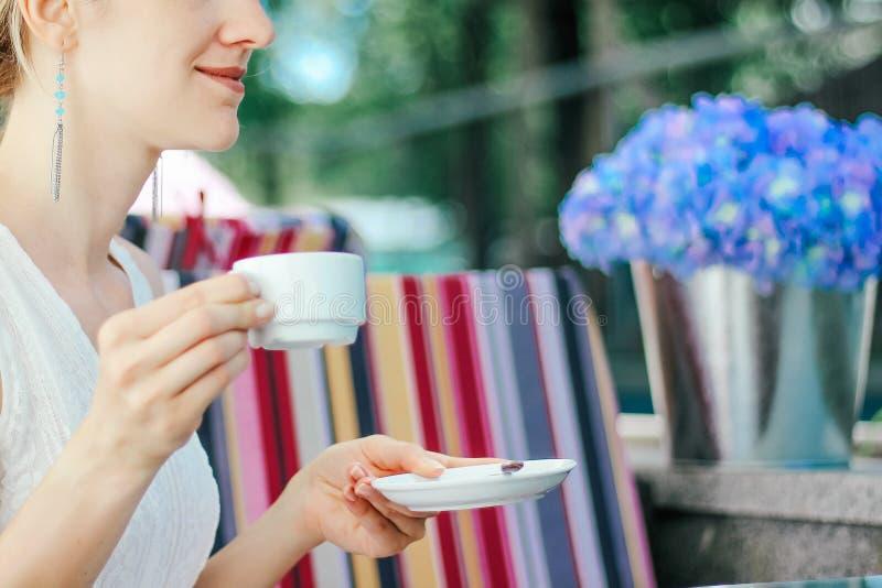 La muchacha hermosa joven en un cierre blanco del vestido para arriba está bebiendo el café en un café al aire libre imágenes de archivo libres de regalías